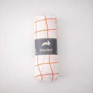 single swaddle blanket with orange crossed stripes rolled in Red Rover packaging