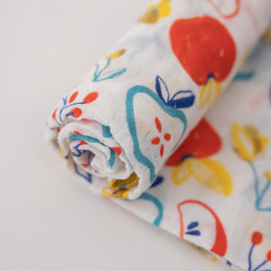single swaddle blanket with colorful apple slices and flowers on it