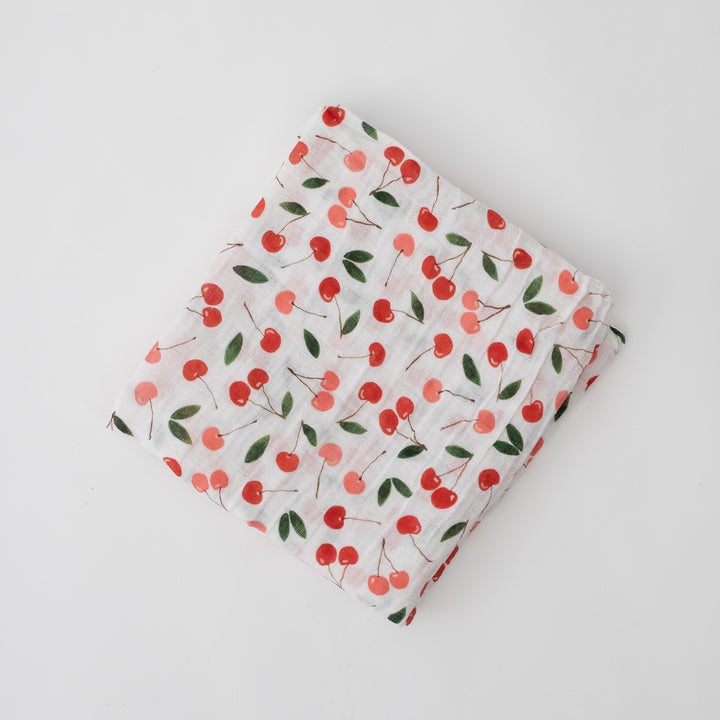 single swaddle blanket with pink and red cherries on a white background