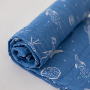 single swaddle blanket with white starts, telescopes, rocket ships, and planets all on a blue background