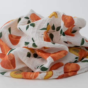 single swaddle blanket with whole and sliced peaches on a white background