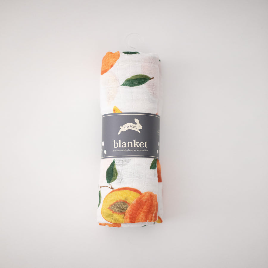 single swaddle blanket with whole and sliced peaches on a white background rolled in Red Rover packaging