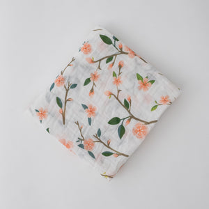 single swaddle blanket with peach blossoms blooming from a tree branch