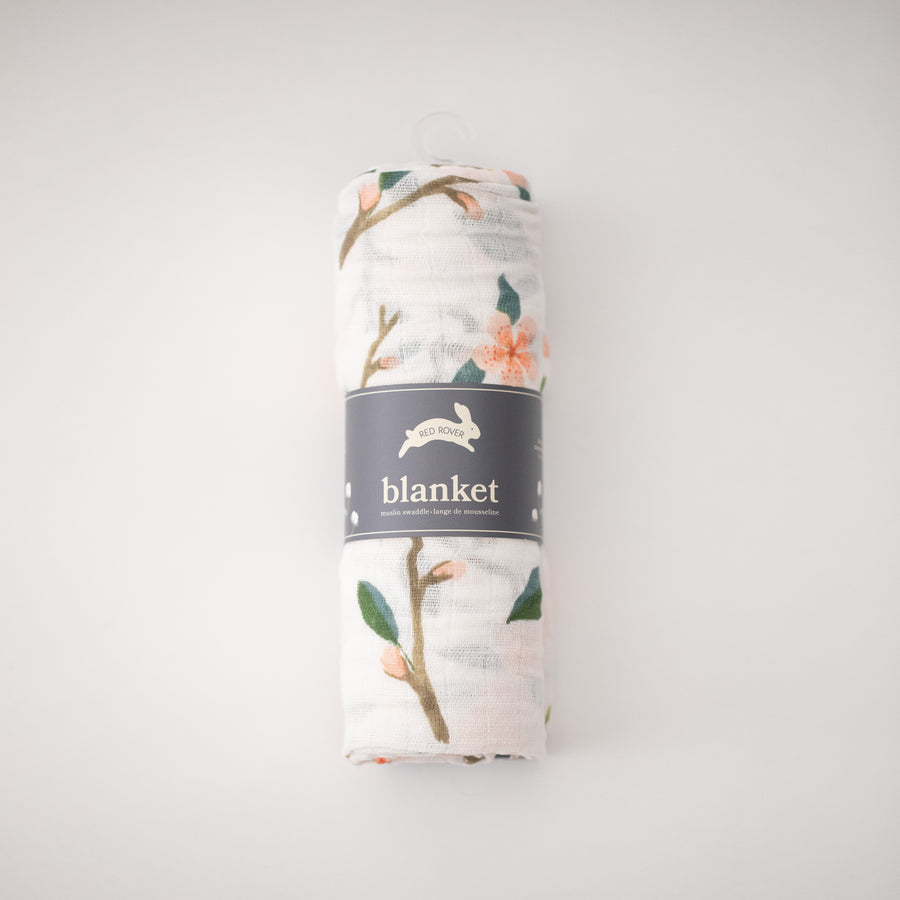 single swaddle blanket with peach blossoms blooming from a tree branch rolled in Red Rover packaging