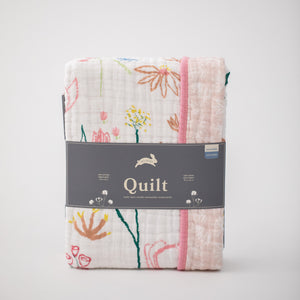 super soft cotton muslin quilt with colorful flowers on a white background and small white flowers on a blush pink background in Red Rover packaging