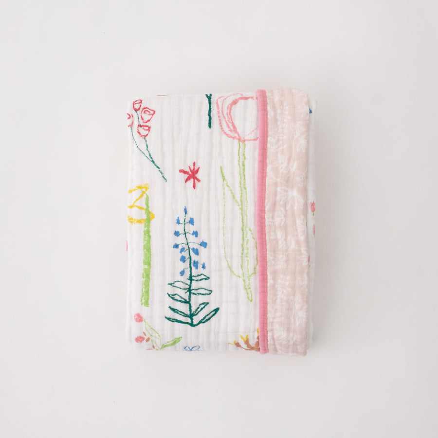 super soft cotton muslin quilt with colorful flowers on a white background and small white flowers on a blush pink background