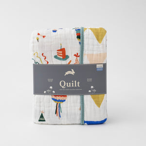 super soft cotton muslin quilt with lots of items you would find at a Mexican fiesta on one side and triangle party banners on the other side in Red Rover packaging