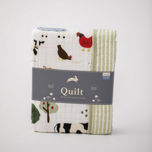 super soft cotton muslin quilt with farm animals on one side and small green stripes on the other side in Red Rover packaging