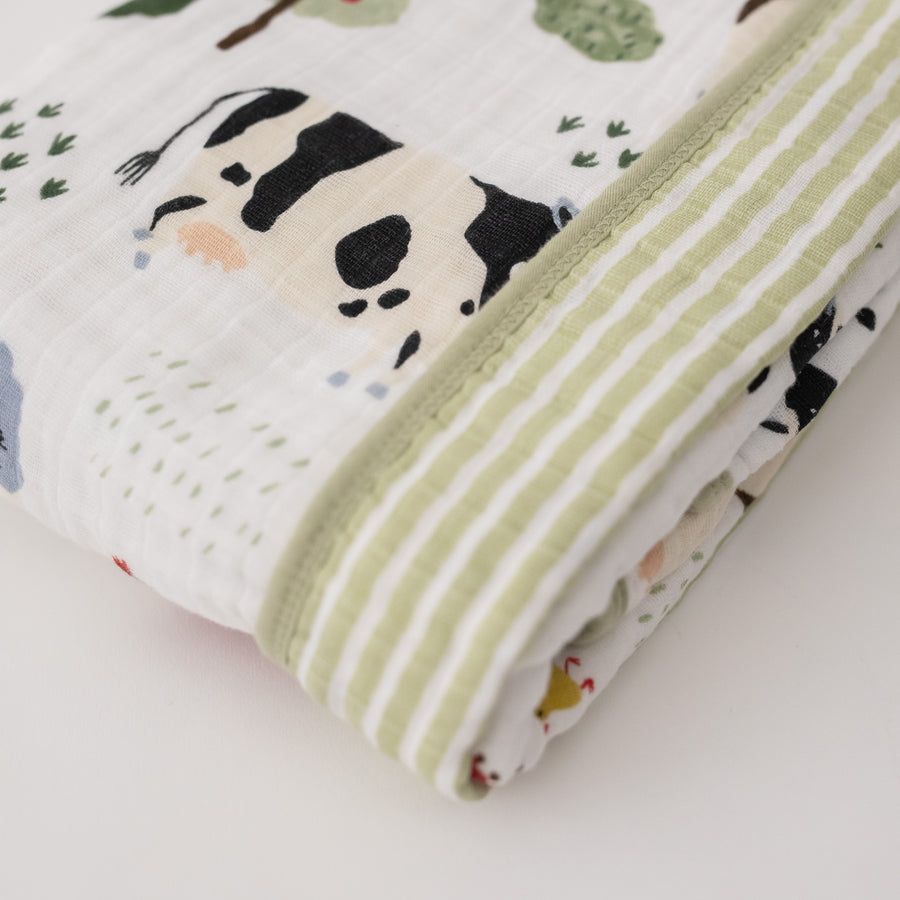 super soft cotton muslin quilt with farm animals on one side and small green stripes on the other side