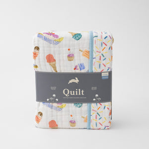 super soft cotton muslin quilt with ice cream cones and other frozen treats on one side and sprinkles on the other side in Red Rover packaging