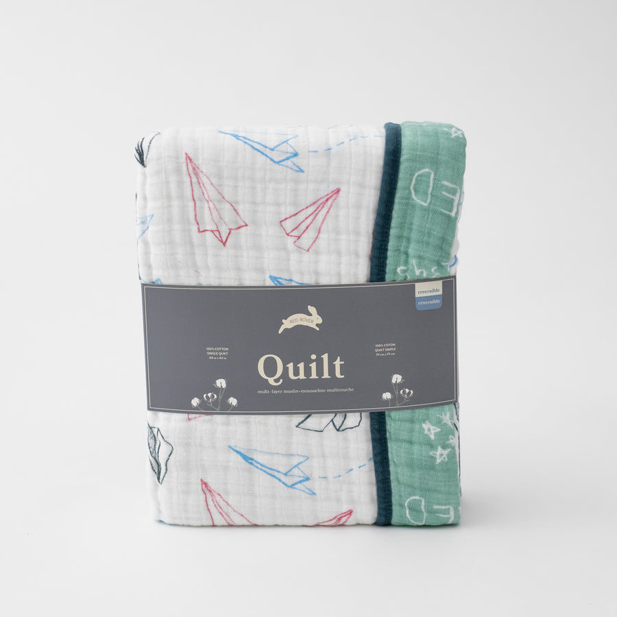 super soft cotton muslin quilt with paper airplanes on one side and a chalk board style print on the other side