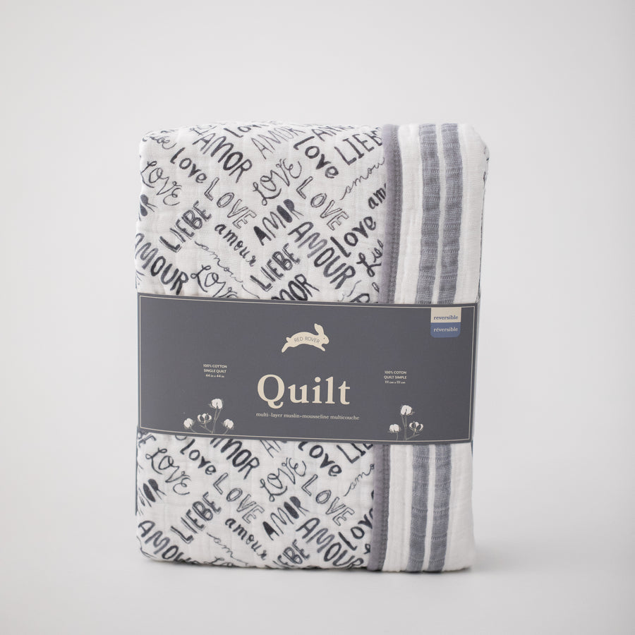 "super soft cotton muslin quilt with the word ""love"" in multiple languages in grey print on one side and double grey stripes on the other side in Red Rover packaging"
