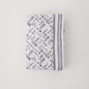 "super soft cotton muslin quilt with the word ""love"" in multiple languages in grey print on one side and double grey stripes on the other side"