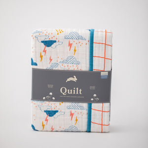 super soft cotton muslin quilt with blue clouds, yellow and pink lightening on one side and orange crossed stripes on the other side in Red Rover packaging