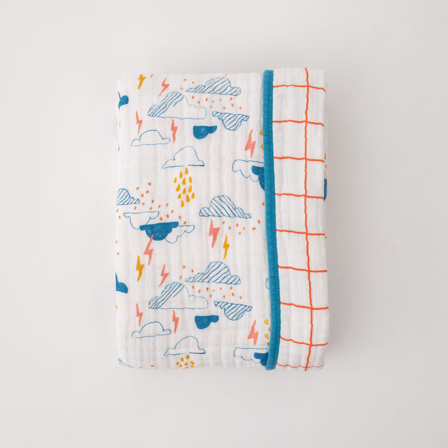 super soft cotton muslin quilt with blue clouds, yellow and pink lightening on one side and orange crossed stripes on the other side