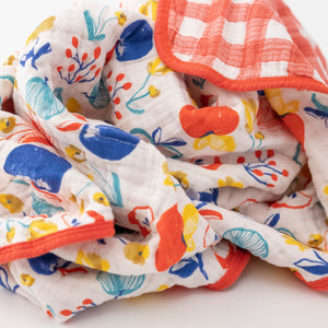 super soft cotton muslin quilt with apple slices on one side and red plaid on the other side all bunched up