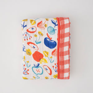 super soft cotton muslin quilt with apple slices on one side and red plaid on the other side