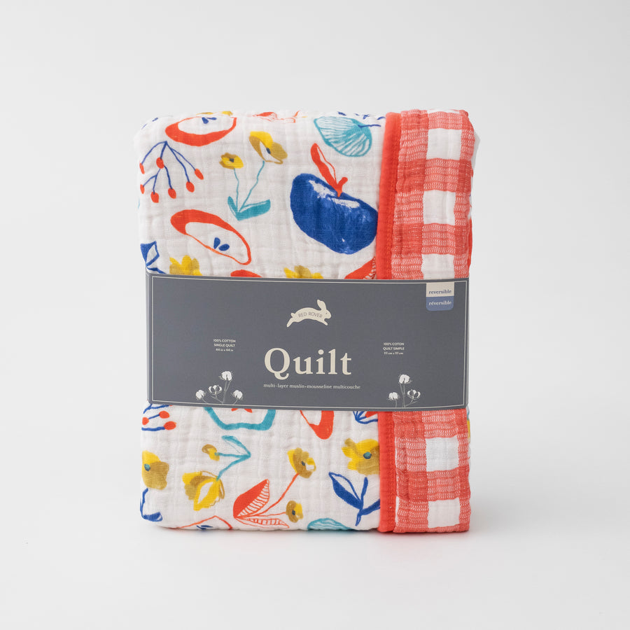 super soft cotton muslin quilt with apple slices on one side and red plaid on the other side in Red Rover packaging