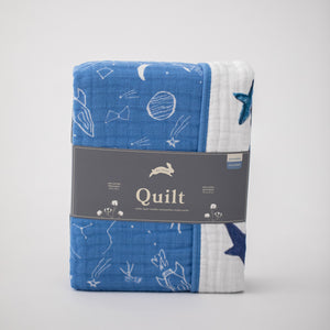 "super soft cotton muslin quilt with white planets, stars, telescopes, and rocket ships all on a blue background on one side and the text ""you are my sun my moon and all my stars"" on the other side in Red Rover packaging"