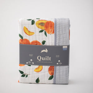 super soft cotton muslin quilt with whole and cut open peaches on one side and grey micro stripes on the other side in Red Rover packaging
