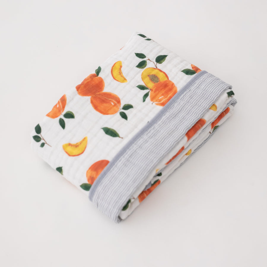 super soft cotton muslin quilt with whole and cut open peaches on one side and grey micro stripes on the other side