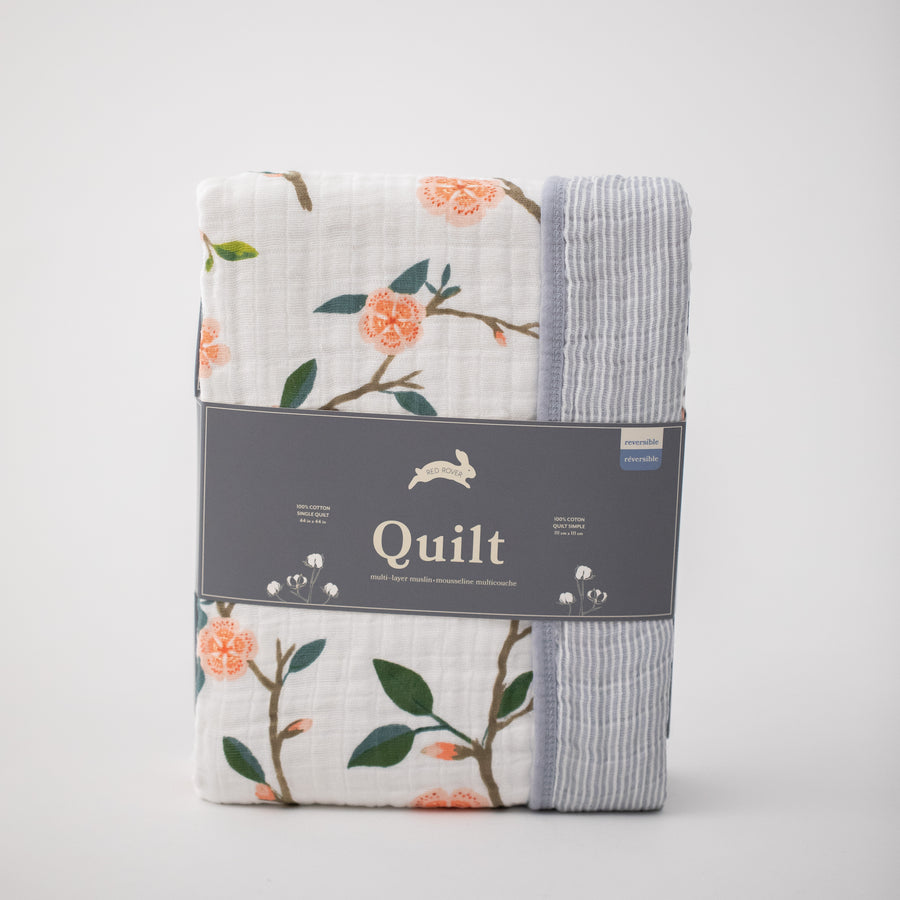 super soft cotton muslin quilt with peach blossoms blooming on a tree branch on one side and grey micro stripes on the other side in Red Rover packaging
