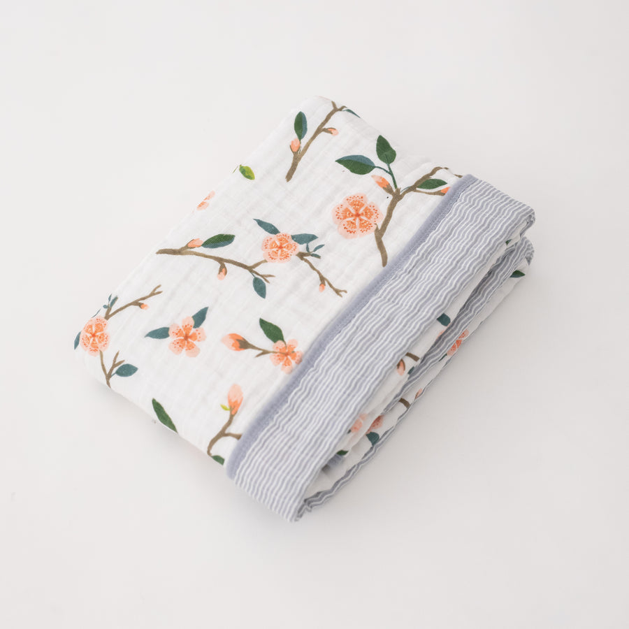 super soft cotton muslin quilt with peach blossoms blooming on a tree branch on one side and grey micro stripes on the other side