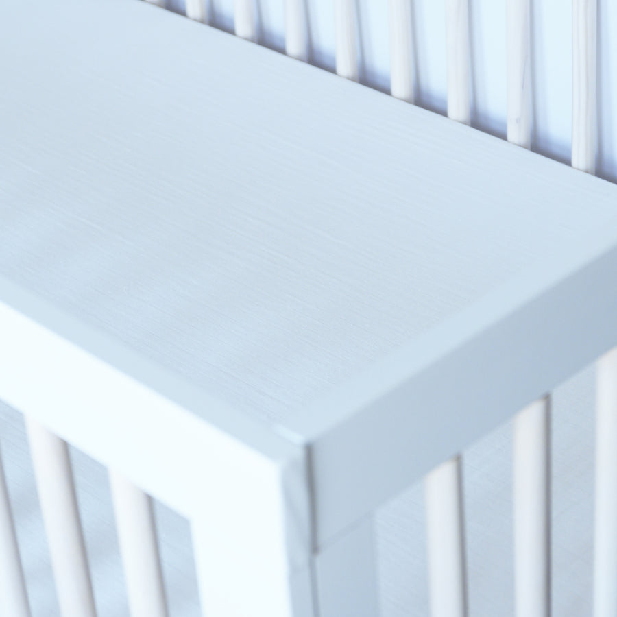 all white cotton muslin crib sheet in a crib