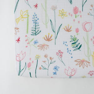 cotton muslin crib sheet with blue, pink, yellow, and red flowers on a white background