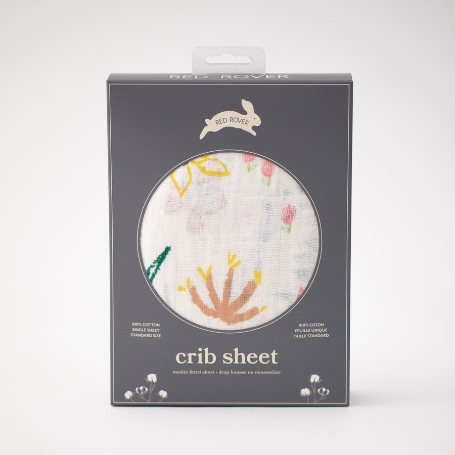 cotton muslin crib sheet with blue, pink, yellow, and red flowers on a white background in Red Rover packaging