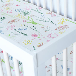 cotton muslin crib sheet with blue, pink, yellow, and red flowers on a white background in a crib