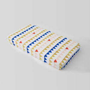 cotton muslin crib sheet with yellow and blue triangles strung together like a party banner