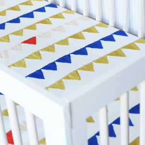cotton muslin crib sheet with yellow and blue triangles strung together like a party banner in a crib