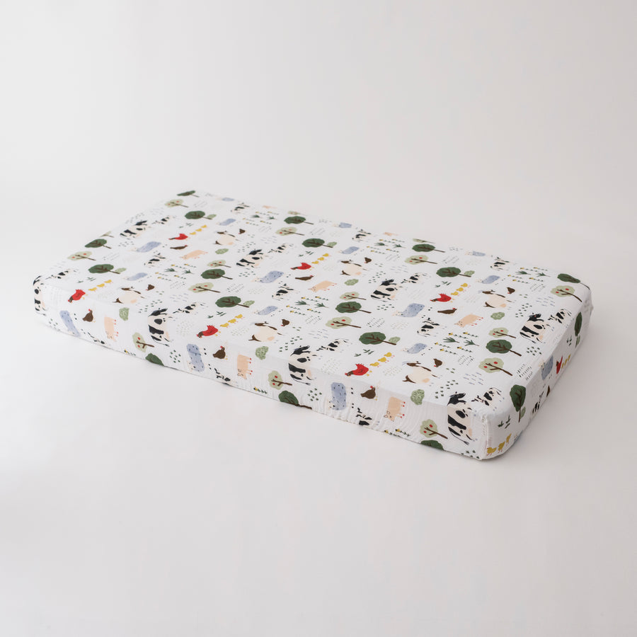 cotton muslin crib sheet with farm animals including cows, chickens, goats, sheep, and pigs