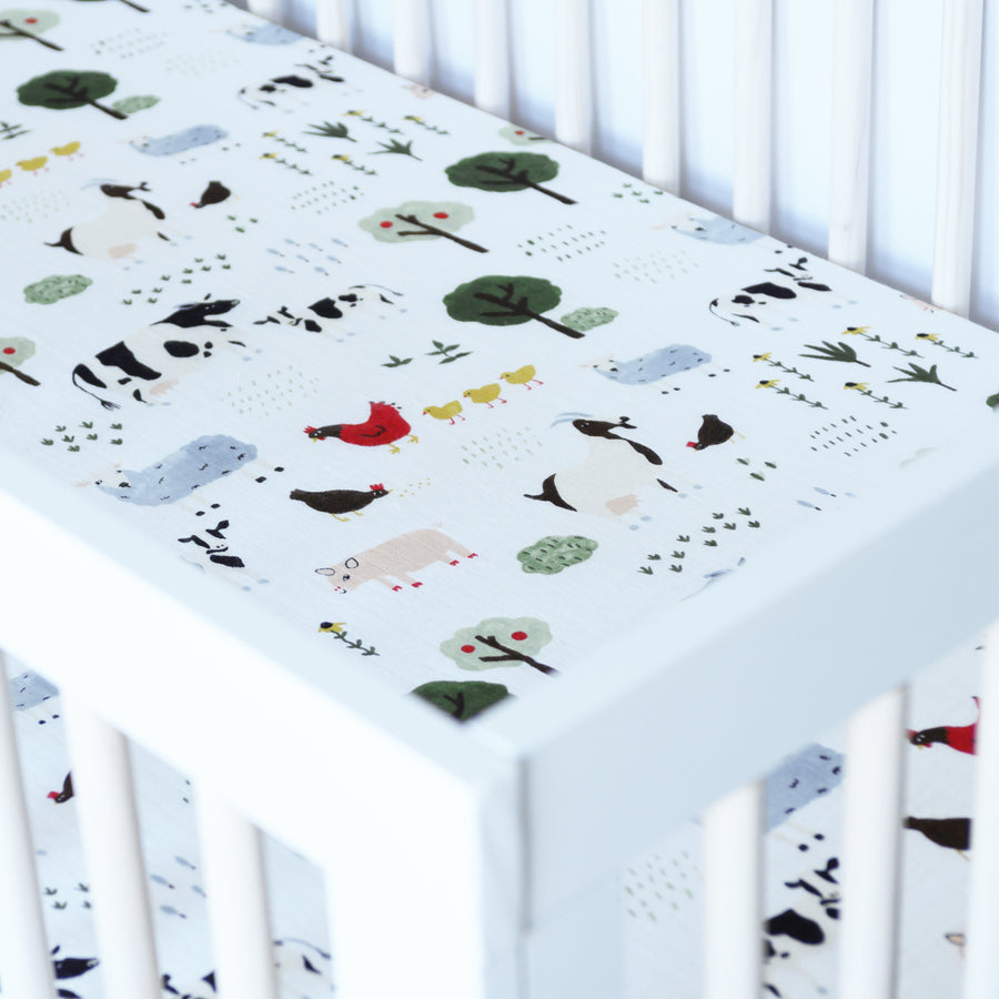 cotton muslin crib sheet with farm animals including cows, chickens, goats, sheep, and pigs in a crib