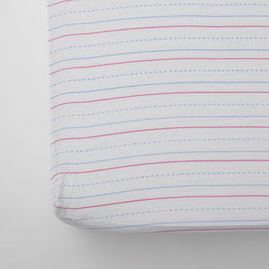 cotton muslin crib sheet with red and blue lines on a white background that looks like a piece of paper