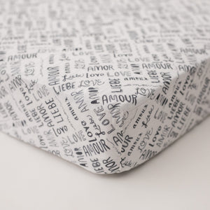 "cotton muslin crib sheet with the word ""love"" in multiple different languages in grey writing on a white background"