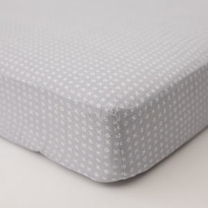 cotton muslin crib sheet with small x's and o's on a grey background