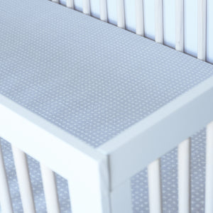cotton muslin crib sheet with small x's and o's on a grey background in a crib