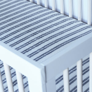 cotton muslin crib sheet double grey stripes on a white background in a crib