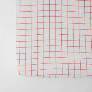 cotton muslin crib sheet with vertical and horizontal orange stripes on a white background