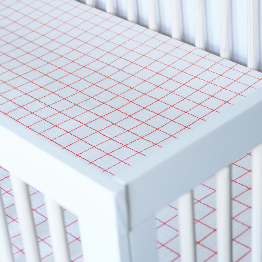 cotton muslin crib sheet with vertical and horizontal orange stripes on a white background in a crib