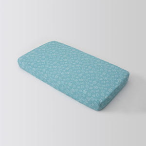 cotton muslin crib sheet with small white flower buds on a teal colored background