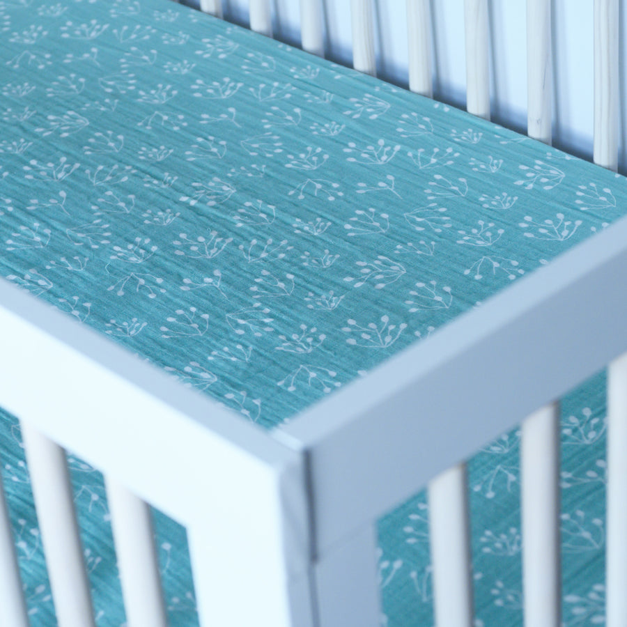 cotton muslin crib sheet with small white flower buds on a teal colored background in a crib sheet