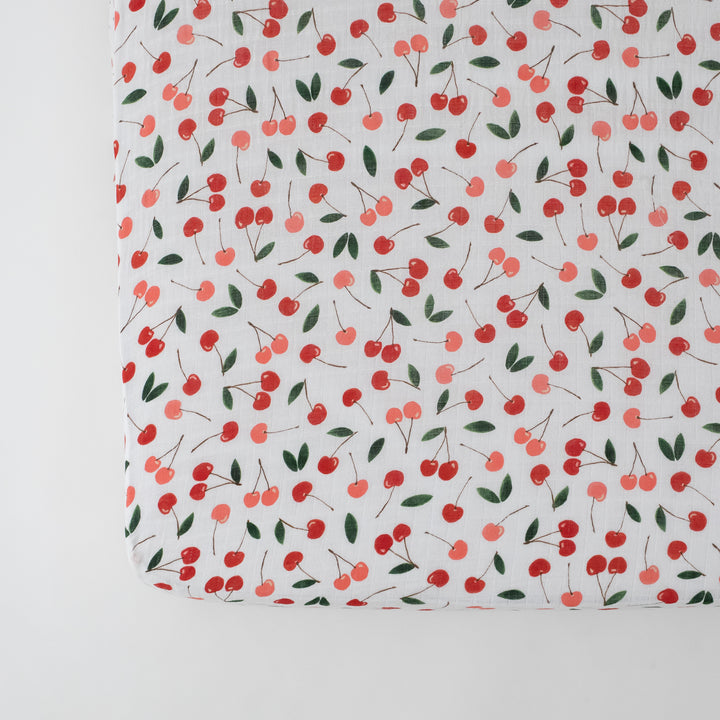 cotton muslin crib sheet with red and pink cherries on a white background