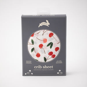cotton muslin crib sheet with red and pink cherries on a white background in Red Rover packaging