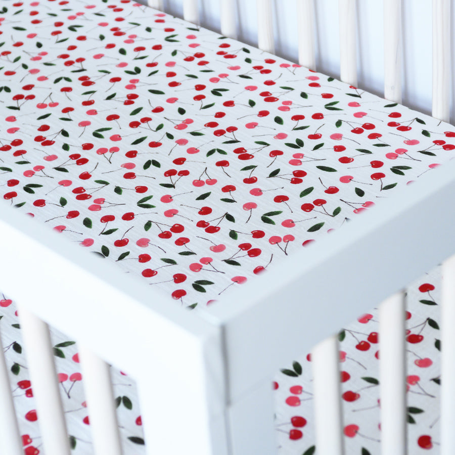 cotton muslin crib sheet with red and pink cherries on a white background in a crib