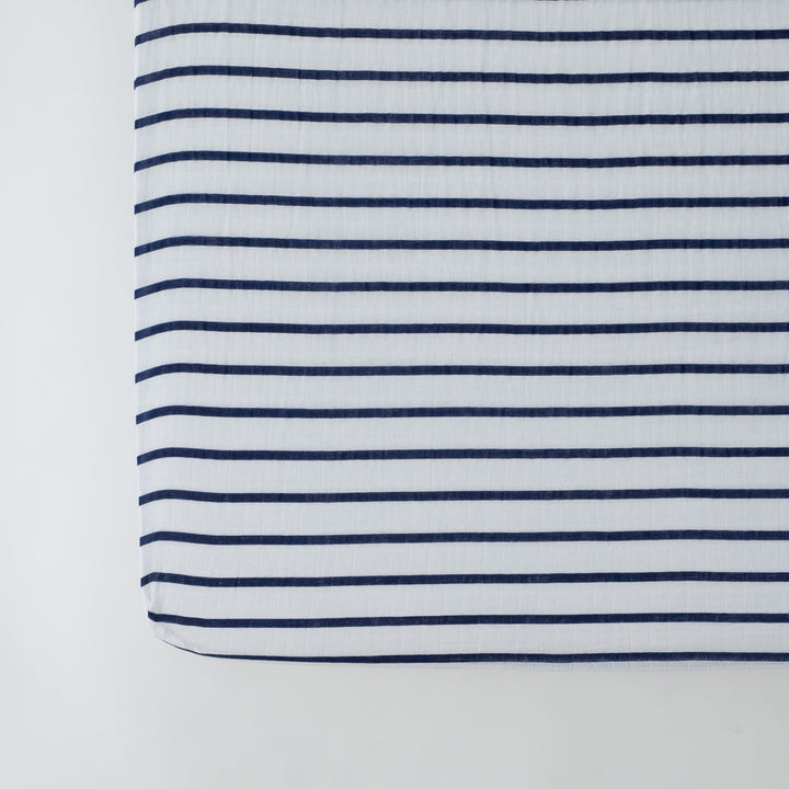 cotton muslin crib sheet with navy stripes on a white background