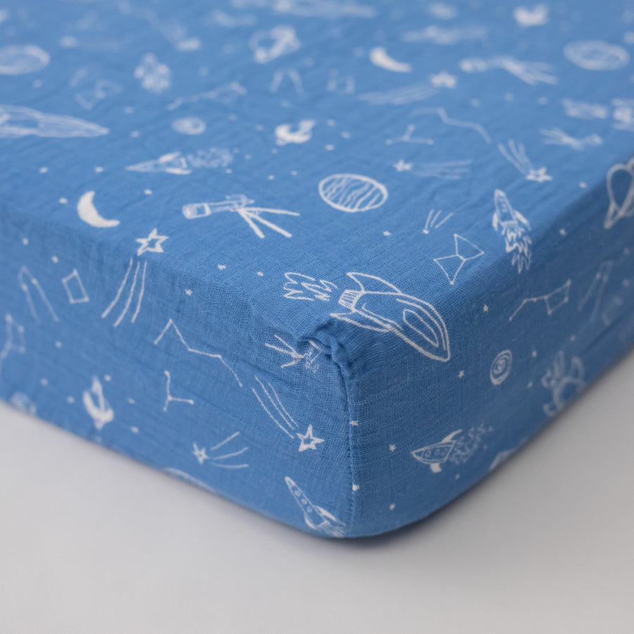 cotton muslin crib sheet with white stars, planets, telescopes, and rocket ships all on a blue background