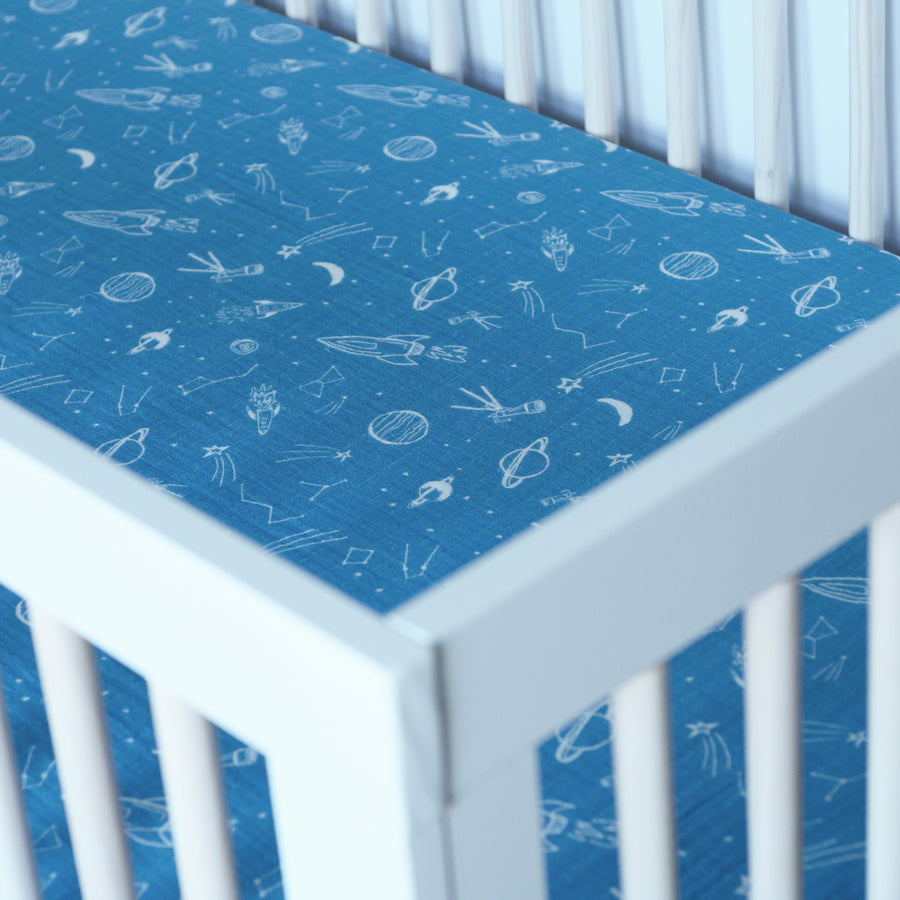 cotton muslin crib sheet with white stars, planets, telescopes, and rocket ships all on a blue background in a crib